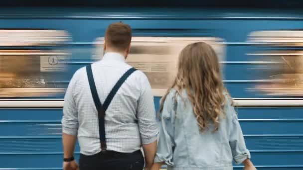 Aşıklar bir metroda duruyor ve önlerinden bir tren geçiyor.