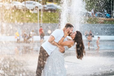 Handsome guy and beautiful girls kissing on the background of a fountain