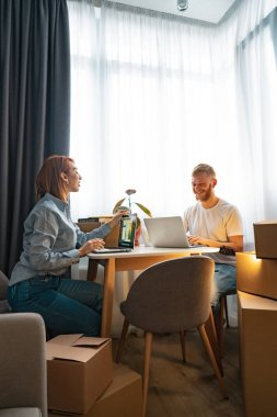 Young man and woman sitting at table, working at laptop in co-working office