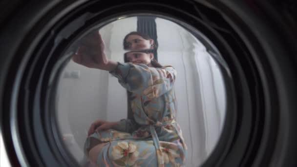 junge Frau zu Hause legt Kleid in die Trocknungsmaschine.