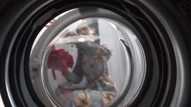 Junge Frau zu Hause legt das Kleid in die Trocknungsmaschine.