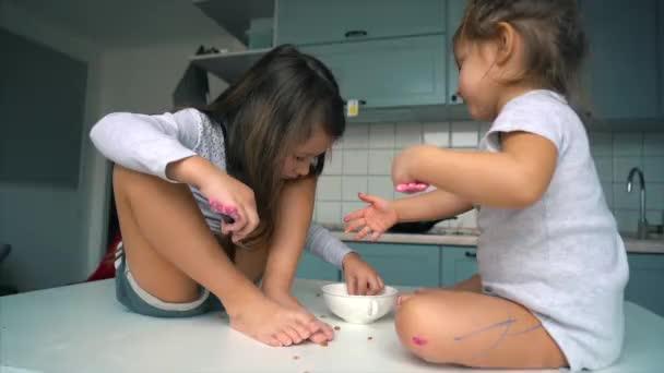 Zwei kleine Mädchen in der Küche sitzen auf dem Tisch.