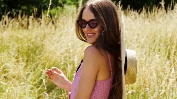 Krásná mladá sexy žena dlouhé vlasy světlý make-up přírodní pozadí krajina suché zásobníku trávy a stromy, zahradní letní model oblečený v bavlněné šaty příslušenství slaměný klobouk sluneční brýle módní styl.