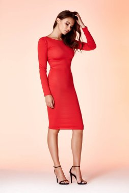 Woman model fashion style red skinny dress beautiful secretary diplomatic protocol office uniform stewardess air hostess business lady perfect body shape brunette hair wear suit elegance casual.