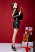 Gyönyörű fiatal csinos nő fényes este smink fényes piros rúzs az ajkakon barna göndör haj ünnepi hangulat kötött tél Karácsony Újév és születésnap Szent Valentin-napi ajándék meglepetés.