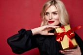 Fotografie Schöne junge hübsche Frau hell Abend Make-up aus leuchtend rotem Lippenstift auf den Lippen blond lockiges Haar festliche Stimmung gestrickt Winter Weihnachten Neujahr und Geburtstag Valentinstag Geschenk Überraschung.
