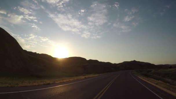 Sluneční paprsky přes klikaté silnici přes Badlands skalní útvary
