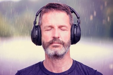 portrait of handsome bearded man with headphones outdoors in the rain