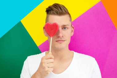 Handsome young blond man holding a heart shaped lollipop stock vector