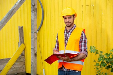 Construction worker with yellow helmet and orange vest holding a folder stock vector
