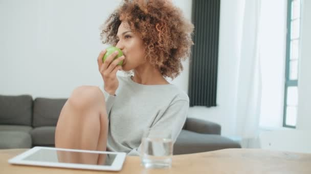 Young woman sitting with green apple at home and smiling at camera.