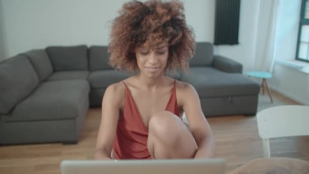 Young Afro American woman using laptop computer while sitting at table.
