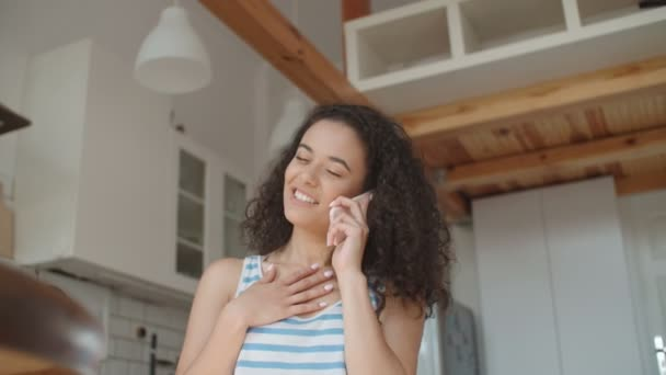 Young woman talking on mobile phone in stylish apartment.