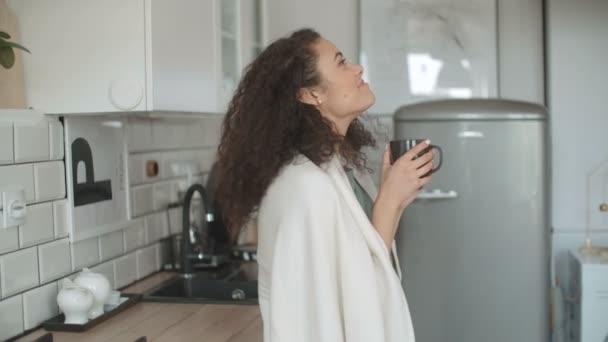 Portrét usmívající se žena pít kávu nebo čaj doma.