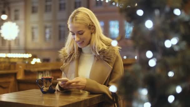 Žena používající smartphone na vánoční trh. Dívka se těší zimních prázdnin. Koncept sociálních sítí, komunikaci, pomocí app. rozmazané vánoční světla na pozadí.