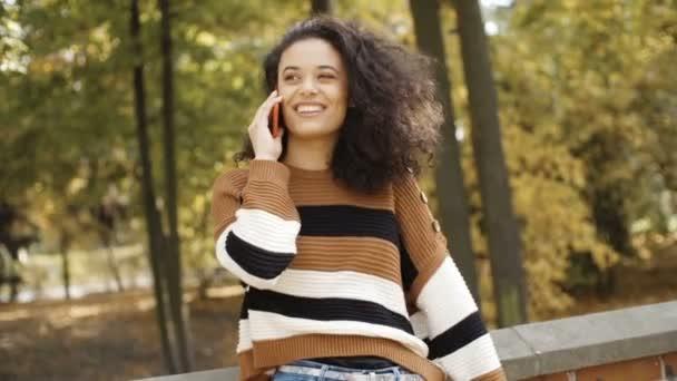 Krásná mladá dívka s tmavými kudrnatými vlasy pomocí její telefon v městském parku.