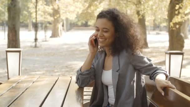 Krásná mladá dívka s tmavými kudrnatými vlasy pomocí svého mobilního telefonu, venkovní.