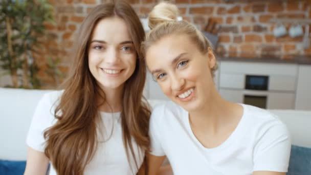 junge Mädchen, die in die Kamera schauen und lächeln. Porträt zweier fröhlicher Teenager-Freundinnen, die sich zu Hause entspannen.