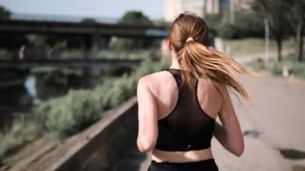 Junge Frau joggt in Flussnähe in der Stadt. Blick von hinten auf eine rennende Frau. Energetische Frau läuft auf Straße