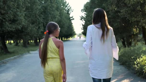 Woman with daughter teenager walk in the park. Happy family - mom and daughter