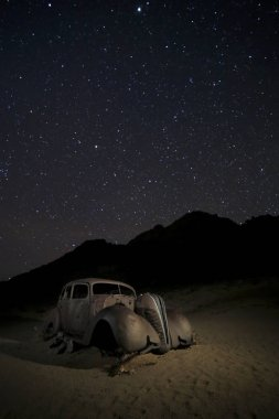 Eski paslı araba açık yıldızlı gökyüzü altında
