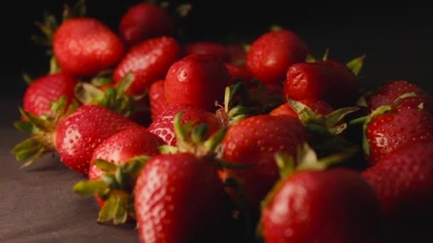 Jahoda na černém pozadí zpomalení boční pohled. Vynikající zralé šťavnaté červené bobule na stole detailní up. Čerstvé jahody se stopkou přírodní eko čisté ovoce. Letní sladký bio produkt pomalé mo