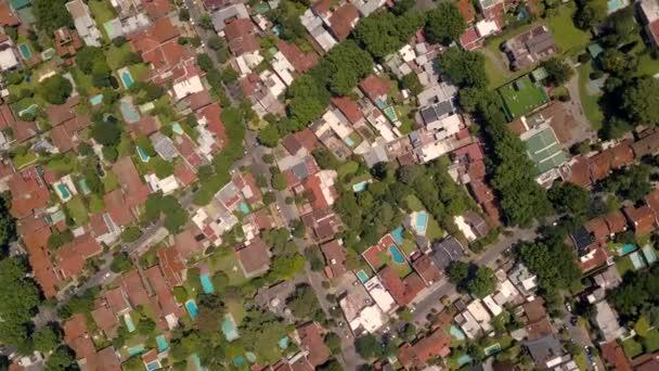 Dron nad předměstím s budovami, domy a řekou v Buenos Aires v letním dni