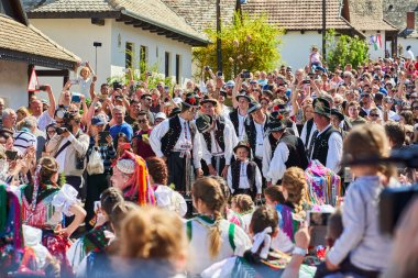 Group of men, dressed in a traditional folk costumes, among tourists during Easter celebration in Holloko village, Hungary country