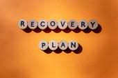 Fotografie Aufschrift des Rettungsplans aus Holzbuchstaben isoliert auf orangefarbenem Hintergrund. Geschäftskonzept. Die Erholung der von der globalen Finanzkrise betroffenen Wirtschaftssektoren. Ansicht von oben. Banner