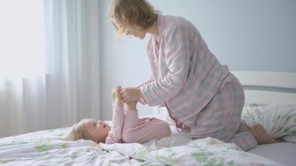 Těhotná matka v pyžamu na posteli líbá své dcery nohy.