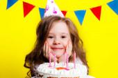 Geburtstagskind von sechs Jahren mit festlicher Torte und Kerzen auf gelbem Hintergrund mit einem Kranz aus bunten Fahnen.