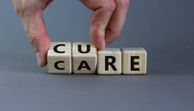 Hand is turning cubes and changes the word 'CARE' to 'CURE'. Business concept. Beautiful grey background, copy space.