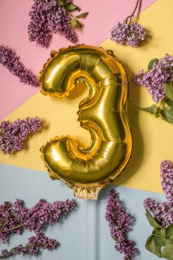 Three year birthday. Number 3 gold foil balloon on colorful festive background with lilac flower blooms decor. Anniversary, celebration concept composition. Flat lay, top view