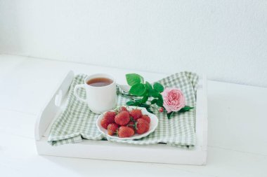 Breakfast on a tray with strawberries. Good morning. Rose