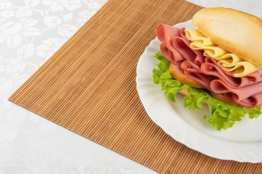 Mortadella sandwich, lettuce and cheese on a white plate and a bamboo mat with white background on a table with white towel, Selective focus.
