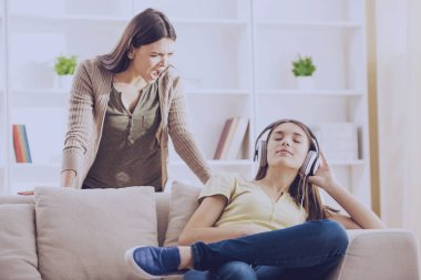Teen closed ears with headphone while mom yells