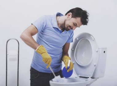 Smiling man is cleaning toilet with brush.