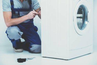 Man is repairing washing machine.
