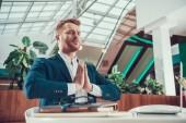 Fotografie Worker man meditating at desk in office.