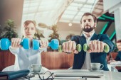 Two workers exercising with dumbbells at desk in office.