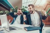 Two men celebrating looking on laptop in office.