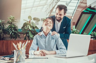 Man massages shoulders of woman in office.
