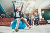 Fotografie Worker exercising on fitness ball in office.