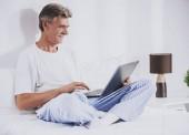 alter Mann benutzt Laptop während er im Bett sitzt.