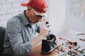 Fotografie Bärtiger alten Mann Reparatur Motherboard von Pc Werkstatt. Arbeiter mit Werkzeugen. Computer-Hardware. Lupe. Rote Mütze. Digitales Gerät. Laptop an der Rezeption. Elektronische Geräte-Konzept