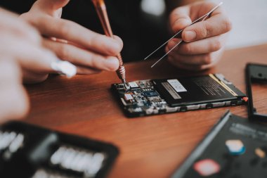 Close up. Young Man Repairing Mobile Phone on Desk