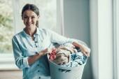 Junge lächelnde Frau hält Korb saubere Kleidung. Hübsches Mädchen Pflege Korb mit Stapel der frischen Kleidung nach der Wäsche. Junge attraktive Frau Hausarbeit mit sauberer Kleidung