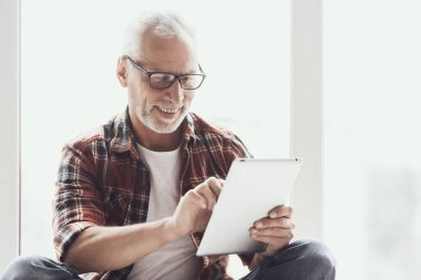 Smiling Mature Man with Beard Using Tablet at Home. Portrait of Casual Adult Happy Man Wearing Glasses enjoing Surfing Internet by Using Gadget. Handsome Bearded Aged Man Reading from Tablet