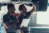 Photo Mechanics Checking Wheel Bearings in Car Workshop. Two Caucasian Adult Technician Master in Uniform Repairing Car. Repairman Looking at Car Using Laptop. Auto Service Concept
