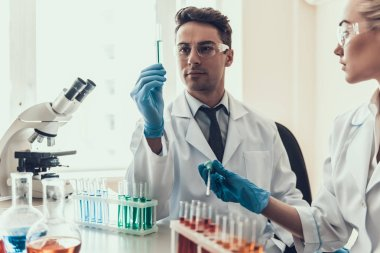 Young Scientists examining Samples in Laboratory. Researchers wearing White Coats Gloves and Protective Glasses examining Chemical Liquid Samples in Flasks. Scientists at Work in Laboratory